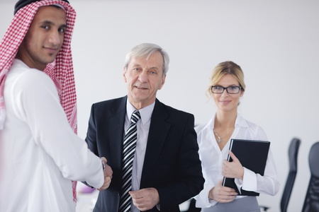 Business meeting - Handsome young Arabic  man presenting his ideas to colleagues and listening for ideas for success investments at bright modern office room Stock Photo - 12708314
