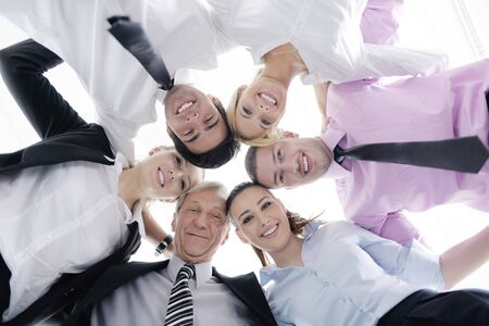 huddle: Closeup of happy business people with their heads together representing concept of ftiendship and teamwork isolated on white background Stock Photo