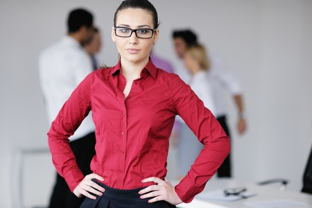 Successful business woman standing with her staff in background at modern bright office Stock Photo - 12766636
