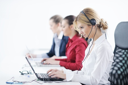 hotline: Pretty young business woman group with headphones smiling at you against white background