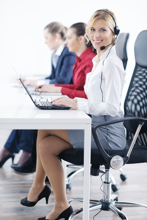 Pretty young business woman group with headphones smiling at you against white background Stock Photo - 12766265