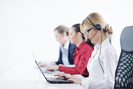 computer operator: Pretty young business woman group with headphones smiling at you against white background