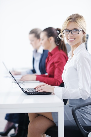 helpline: Pretty young business woman group with headphones smiling at you against white background