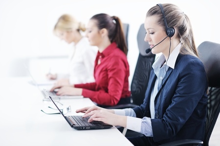 phone operator: Pretty young business woman group with headphones smiling at you against white background