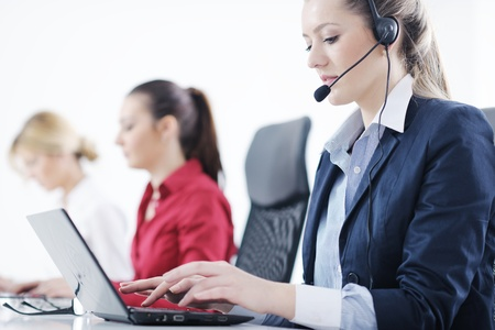 contact center: Pretty young business woman group with headphones smiling at you against white background