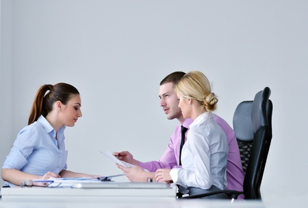 Group of young business people sitting in board room during meeting and discussing with paperwork Stock Photo - 12916124