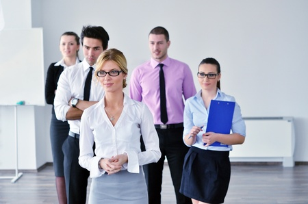Successful business woman standing with her staff in background at modern bright office Stock Photo - 12915924