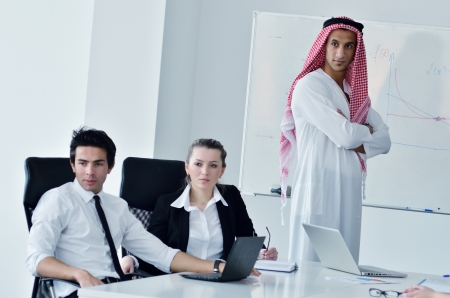 Business meeting - Handsome young Arabic  man presenting his ideas to colleagues and listening for ideas for success investments at bright modern office room Stock Photo - 12915466