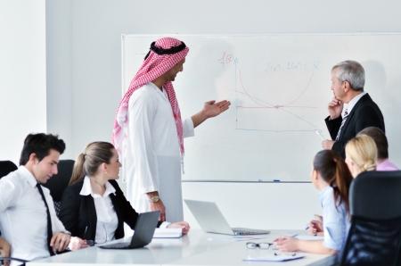 hombre arabe: Reuni�n de negocios - Hermoso hombre �rabe joven con sus ideas a los compa�eros y escucha de las ideas para las inversiones de �xito en la habitaci�n luminosa oficina moderna