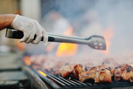 Barbecue with chicken  on grill, fire and smoke in background photo