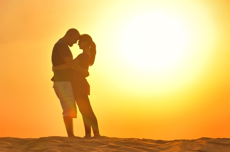 relaxed young pasionate couple enjoying the sunset  beauty on their honeymoon, on a desert with orange background Stock Photo