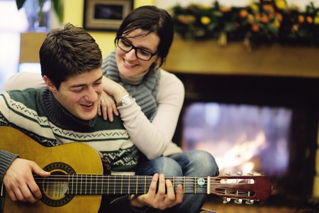happy Young romantic couple sitting on sofa in front of fireplace at winter season in home Stock Photo - 13112454