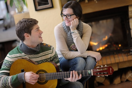 happy Young romantic couple sitting on sofa in front of fireplace at winter season in home Stock Photo - 13112603