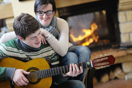 happy Young romantic couple sitting on sofa in front of fireplace at winter season in home photo