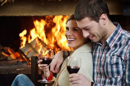 couple winter: happy Young romantic couple sitting on sofa in front of fireplace at winter season in home Stock Photo