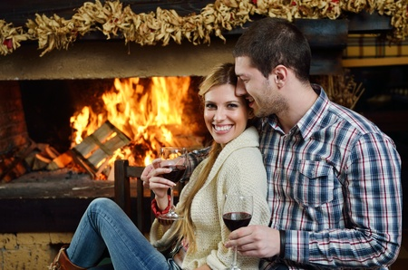 happy Young romantic couple sitting on sofa in front of fireplace at winter season in home Stock Photo - 13112587