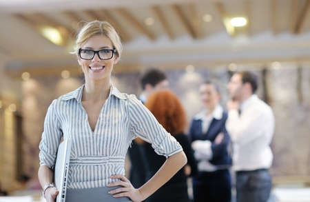 business woman standing with her staff in background at modern bright office conference room Stock Photo - 13112484
