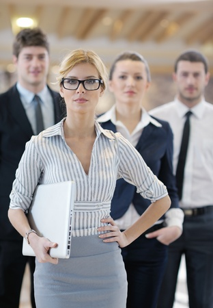 business woman standing with her staff in background at modern bright office conference room Stock Photo - 13112509