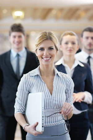 business woman standing with her staff in background at modern bright office conference room Stock Photo - 13112619