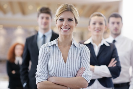 business woman standing with her staff in background at modern bright office conference room Stock Photo - 13112585