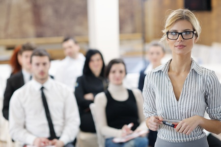 business woman standing with her staff in background at modern bright office conference room Stock Photo - 13112586