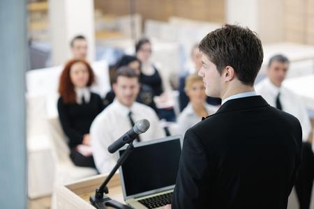 conferentie: jonge mannelijke zakenman het geven van een presentatie op een bijeenkomst seminar op moderne conferentieruimte op een tafel boord