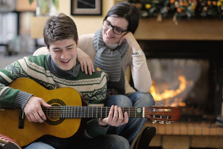 happy Young romantic couple sitting on sofa in front of fireplace at winter season in home Stock Photo - 13112515