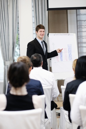 young  male business man giving a presentation at a  meeting seminar at modern conference room  on a table board Stock Photo - 13112516
