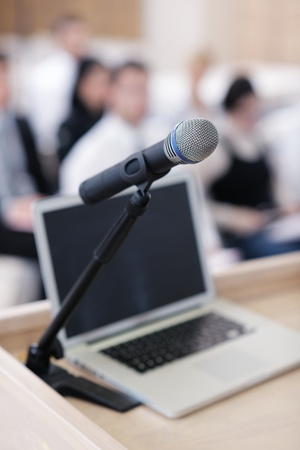 center table: business laptop and microphotone at podium on seminar conference education Stock Photo