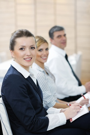 business woman standing with her staff in background at modern bright office conference room Stock Photo - 13180593