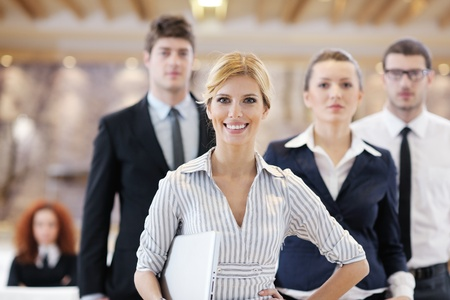 business women: business woman standing with her staff in background at modern bright office conference room