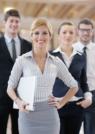 business woman standing with her staff in background at modern bright office conference room Stock Photo - 13180704