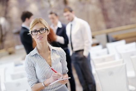 business woman standing with her staff in background at modern bright office conference room Stock Photo - 13180596