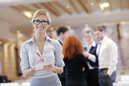 business woman standing with her staff in background at modern bright office conference room Stock Photo - 13180699
