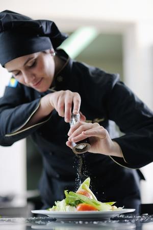 mooie jonge chef-kok vrouw voor te bereiden en decoreren van lekker eten in keuken