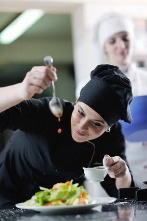 chef cooking: beautiful young chef woman prepare and decorating tasty food in kitchen