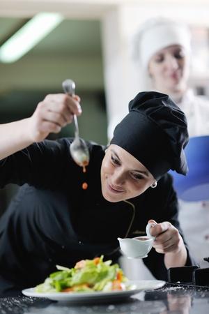 cooking chef: hermosa mujer joven chef prepare y sabrosa comida en la cocina de la decoraci�n Foto de archivo