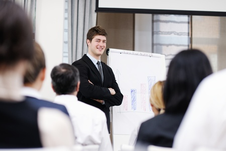 young  male business man giving a presentation at a  meeting seminar at modern conference room  on a table board Stock Photo - 13276468