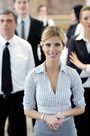 business woman standing: business woman standing with her staff in background at modern bright office conference room