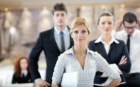 business woman standing with her staff in background at modern bright office conference room photo