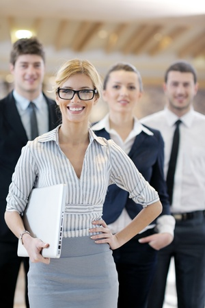 business woman standing with her staff in background at modern bright office conference room Stock Photo - 13276399
