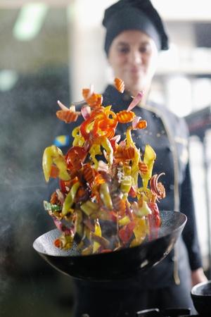 chef cocinando: hermosa joven chef prepare la mujer y la comida sabrosa decoración en la cocina