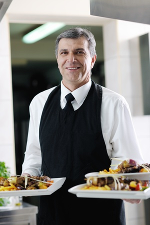 male chef presenting food meal in kitchen photo