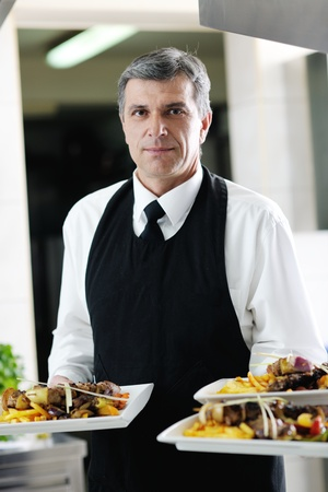 steward: male chef presenting food meal in kitchen Stock Photo