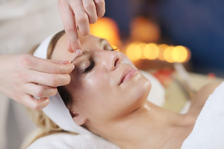 Bella giovane donna in SpA e wellness. Faccia posteriore e stone massage photo