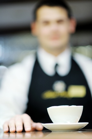 Barista prepares cappuccino in his coffee shop photo