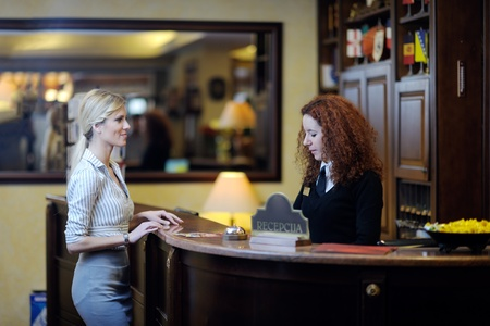 reception counter: business woman  at the reception of a hotel checking in