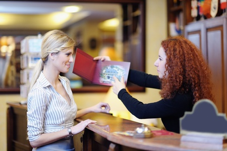 hotel reception: business woman  at the reception of a hotel checking in