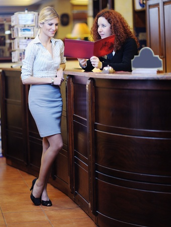 checking in: business woman  at the reception of a hotel checking in