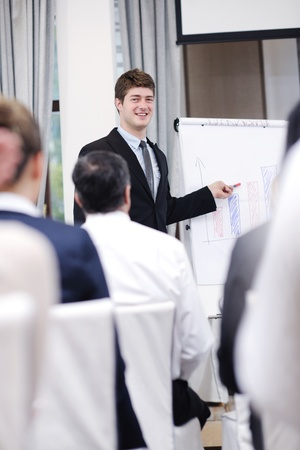 young  male business man giving a presentation at a  meeting seminar at modern conference room  on a table board Stock Photo - 13478090